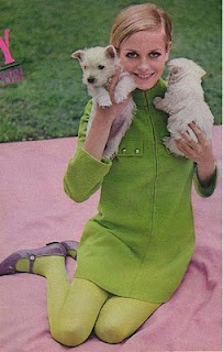 Twiggy embodies the 60s mod look with a pixie hair cut and a monochrome ensemble consisting of a shift mini dress and bright-colored tights.
