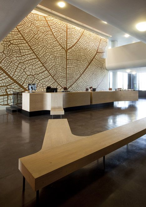 The tree motif continues inside the building, with a veined pattern covering a…