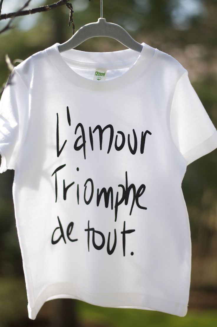 "Hand printed on Royal Apparel Organic Kids Fine Jersey Short Sleeve Tee using eco-friendly, water based inks. $1.00 (cad) for every ""L'amour Triomphe de tout"" shirt sold will be donated to the ""Save the Children"" organization.'"