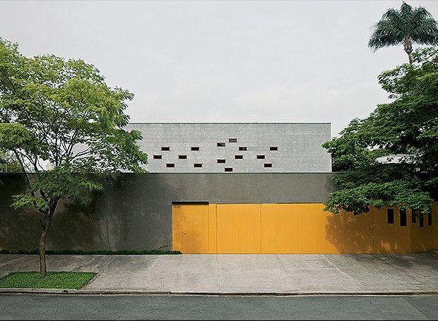 Fachada principal | A retirada do telhado convencional permitiu a forma de caixa. As linhas retas são reforçadas pelas janelinhas retangulares com vidro fixo e freijó, da Nilson Caixilhos, e pelo portão de chapas metálicas com acabamento de tinta amarela