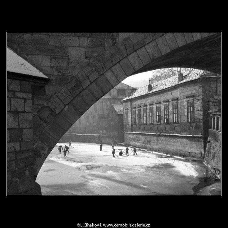 Kluci na bruslích (1414-4) • Praha,prosinec 1961 • | černobílá fotografie, Čertovka, Kampa, bruslení, hokej, kluci, oblouk mostu, sníh |•|black and white photograph, Prague|