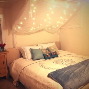 canopy over bed with twinkle lights behind it, this is my kind of bed. :-)