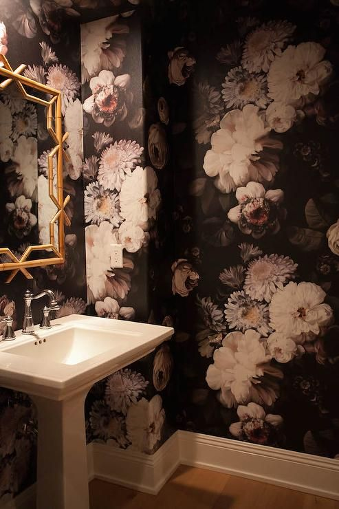 Black and gold powder room features walls clad in black and white floral wallpaper, Ellie Cashman Dark Floral Wallpaper, lined with a pedestal sink and a gold bamboo mirror, Serena & Lily Lanai Mirror.