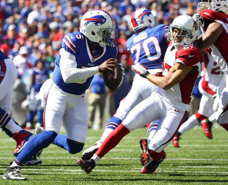 Buffalo Bills quarterback Tyrod Taylor (5) runs under pressure from Arizona Cardinals defensive back Tyvon Branch (27) during the first half of an NFL football game on Sunday, Sept. 25, 2016, in Orchard Park, N.Y.