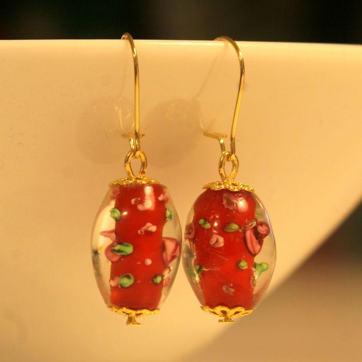 Punaisista lamppuhelmistä tehdyt korvakorut, joissa kullanväriset, nikkelittömät koukut ja koristeosat.
