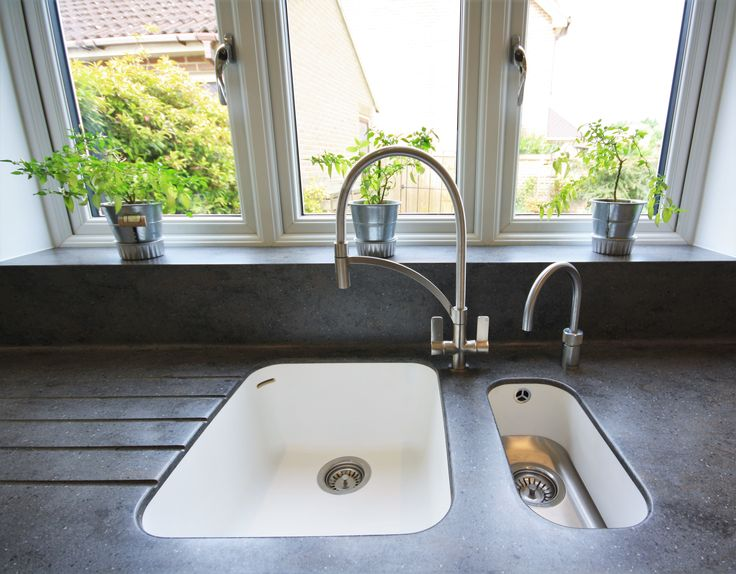 Corian, Lava Rock worktops with a bowl and a half sink in Glacier White. These sinks have a completely seamless finish as they are moulded to the worktop. Designed, Supplied and installed by Kitchencraft, Witham Essex.