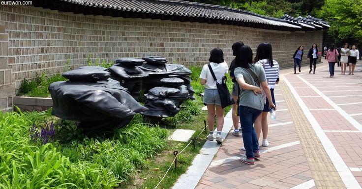 Estatuas Jangdockdae de una familia achatada detrás del palacio Deoksugung en el centro de Seúl, con y sin nieve.