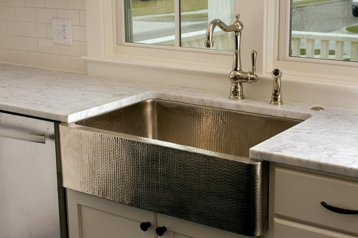 Stunning kitchen features a stainless steel hammered apron sink paired with a gooseneck faucet beside a stainless steel dishwasher placed under windows.