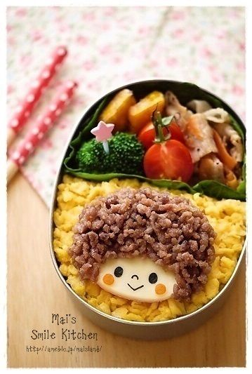 Afro girl bento Ground beef for hair, mozzarella cheese or a round piece of white toast for the face, served on a bed of macaroni and a side of broccoli