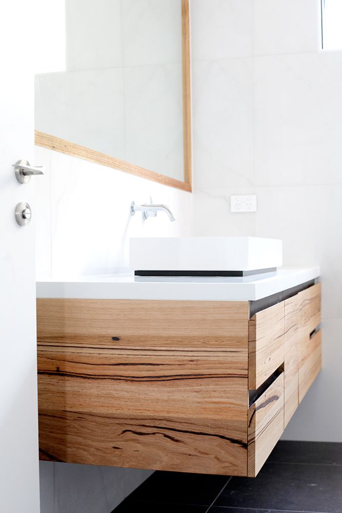 Custom made timber and stone bathroom vanity. The Tathra vanity features recycled Messmate timber, pure white caesarstone and black shadow lines. This modern vanity is perfect to add that luxe spa touch to your bathroom.