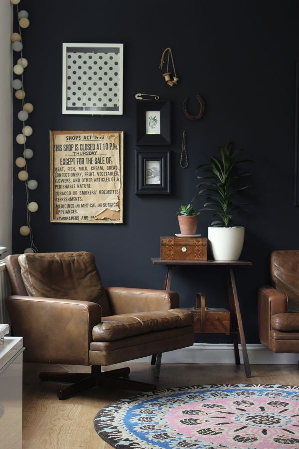 Black feature wall with brown leather and wood