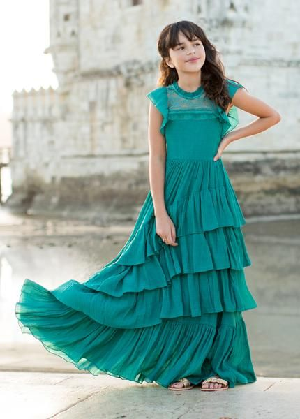 299f1615cd8b4 Timeless and elegant, this maxi dress features flounced, cap sleeves, a  high lace neckline, and cascading tiers of asymmetrical ruffles.