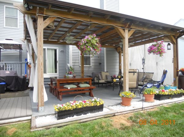 Tin roof pergola with curtains and imagine this. . . A colonial provincial style rustic chandelier hanging from it. And an inviting table with the grill going off to the side. ahhhhh bliss..
