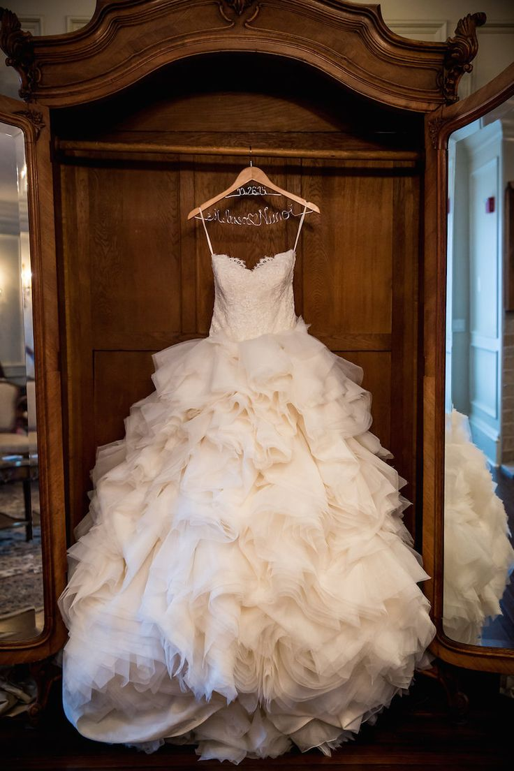 Ball Gown with Dramatic, Ruffled Skirt on Hanger | Photography: Danette Pascarella Photography. Read More: http://www.insideweddings.com/weddings/catholic-ceremony-estate-reception-with-travel-themed-details/696/