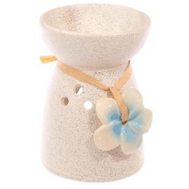 Een leuke Wax-Melt Brander van keramiek. Deze Wax-Melt brander  is versierd met een bloem van keramiek welke om de oliebrander gebonden is.    Dankzij het grote gat in de brander kunt u het waxinelichtje zonder gevaar in de brander zetten en komt er voldoende zuurstof in de brander. De hitte die ontstaat zal de geur wax-melt laten smelten en verspreidt zo de geur.    Vorm: rond Materiaal: keramiek Kleur: crème  Bloem: Blauw  Hoogte:  ca 11 cm Diameter: ca 8 cm