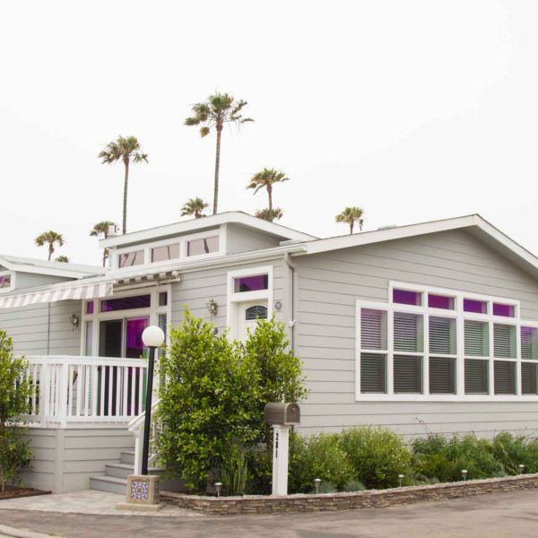 """This popular """"open concept"""" beach style cottage home has a traditional white kitchen with stainless steel appliances over looking its large expansive great room that has been styled with lots of transom windows, skylights, and clerestories overhead."""