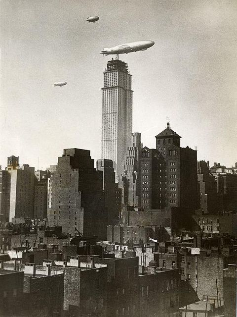 The American airship ZR 3 Los Angeles flying near the Empire State Building under construction. The Zeppelin, built as LZ 126, is accompanied by some blimps. 29 October 1930 via Dutch Nationaal Archief
