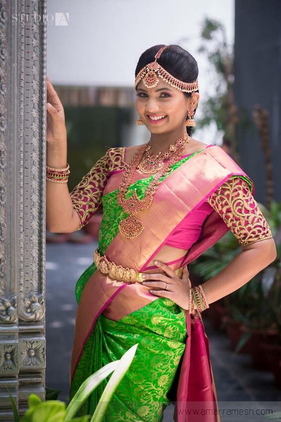 South Indian bride. Gold temple bridal jewelry. Jhumkis.Green kanchipuram sari with contrast pink blouse.Braid with fresh jasmine flowers. Tamil bride. Telugu bride. Kannada bride. Hindu bride. Malayalee bride.Kerala bride.South Indian wedding