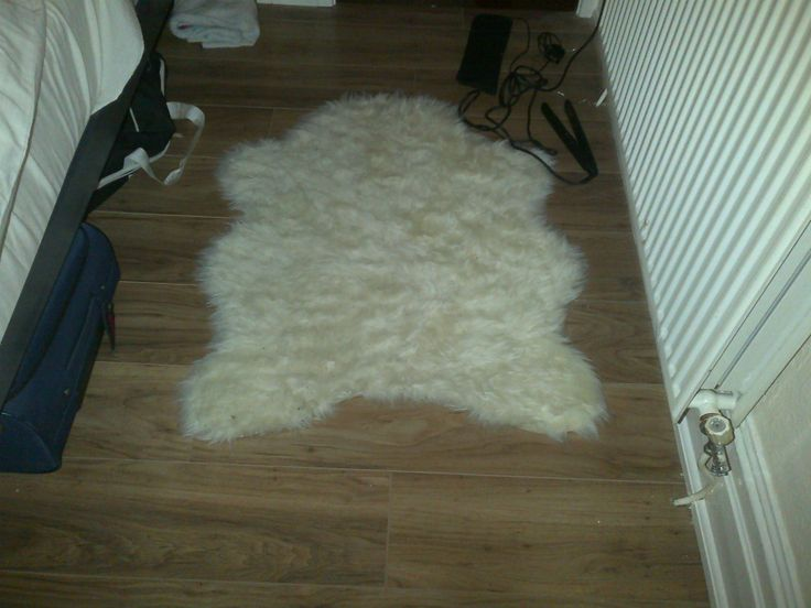 white faux sheepskin rug plus wooden floor and white fence for home interior design ideas