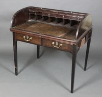 Lot 1102 A Georgian mahogany writing table enclosed by a D shaped tambour shutter, the interior fitted pigeon holes, drawers and 2 candle slides, the base fitted 2 long drawers and 2 brushing slides, est £300-500
