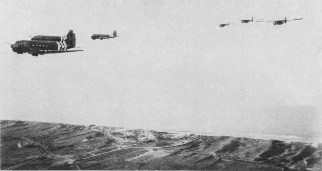 C-47s of the 9th Air Force Troop Carrier Command tow reinforcements in CG-4 gliders across the Normandy beaches on June 6, 1944 (Image).