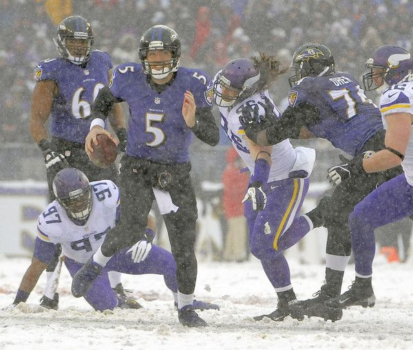Ravens quarterback Joe Flacco, center, scrambles away as right tackle Michael Oher, right, blocks the Vikings' Brian Robison in the first quarter.