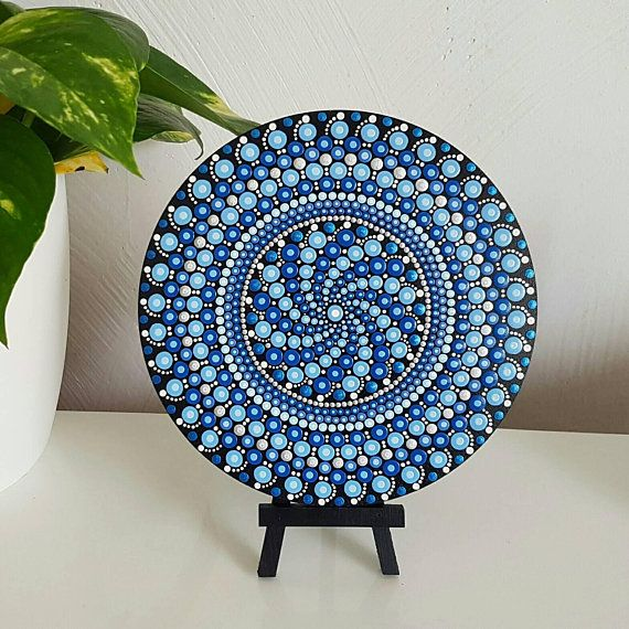 This hand-painted chakra mandala dot art painting is made on a round wood 18cm slice from the French Riviera. It is painted all black, with detailing in a variety of blue shades finished with a lighter shade of each colour and white. This art will brighten any home. It is a beautiful