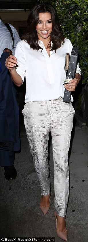 Lucky lady: Eva appeared to be carrying a gift as she showed off her sophisticated chic style in a white blouse, silver snakeskin-printed slacks and nude pumps