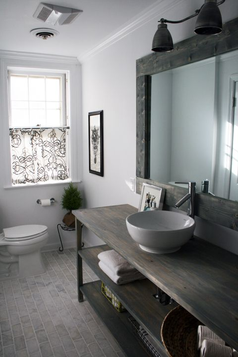 Loving this bathroom for its tiles, the mirror and the wooden table which the fab sink sits on.