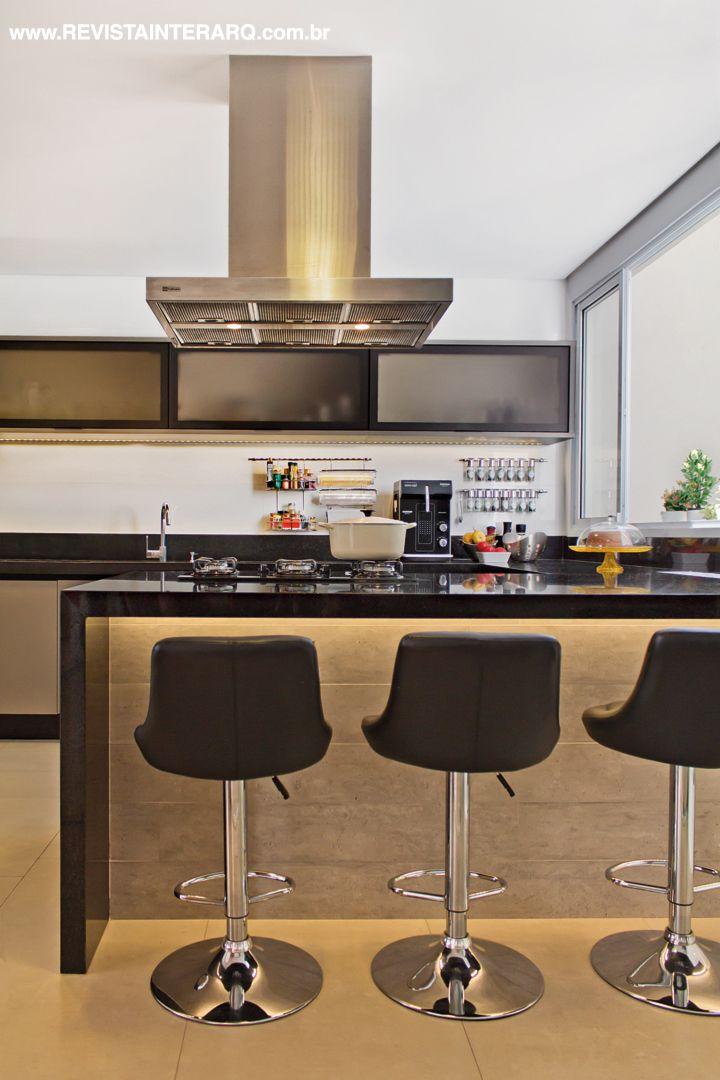 Na cozinha, bancadas em granito Preto Absoluto (Rolsilva Marmoraria) e o revestimento com textura concreto (Ornamentare) imprimem sofisticação