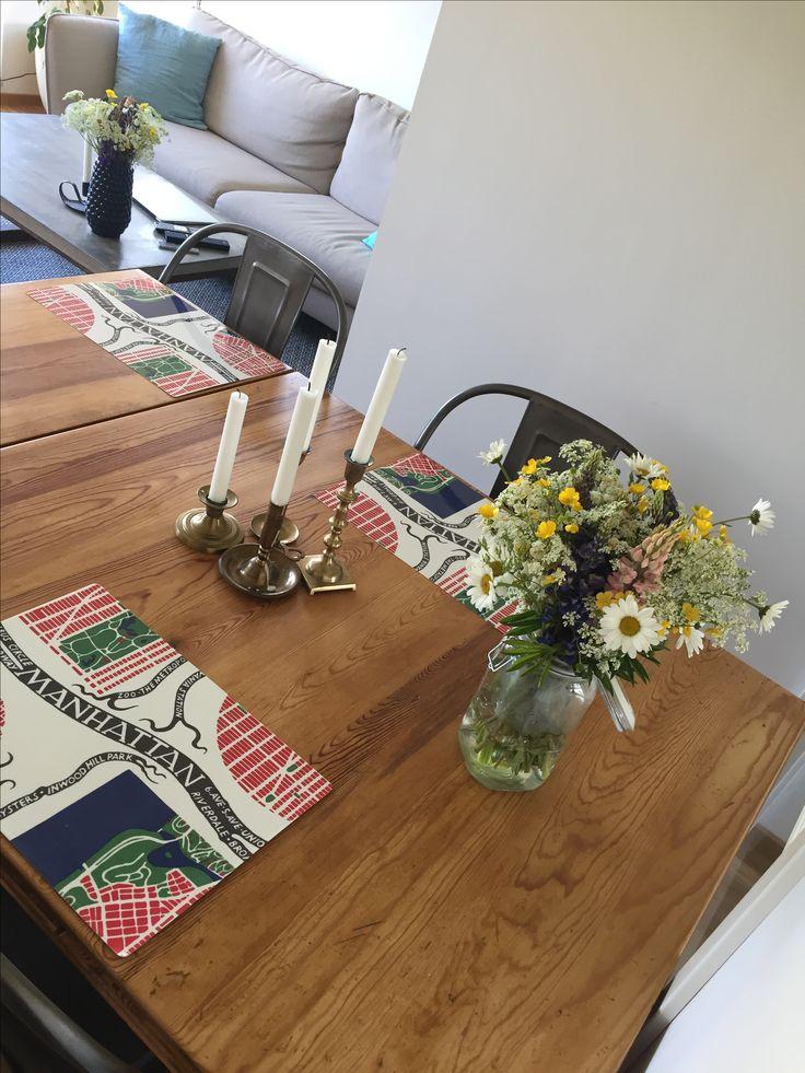 Antikt ärvt köksbord med underlägg från svenskt tenn, loppisfyndade mässingsljusstakar och egenplockad blombukett från Midsommar.
