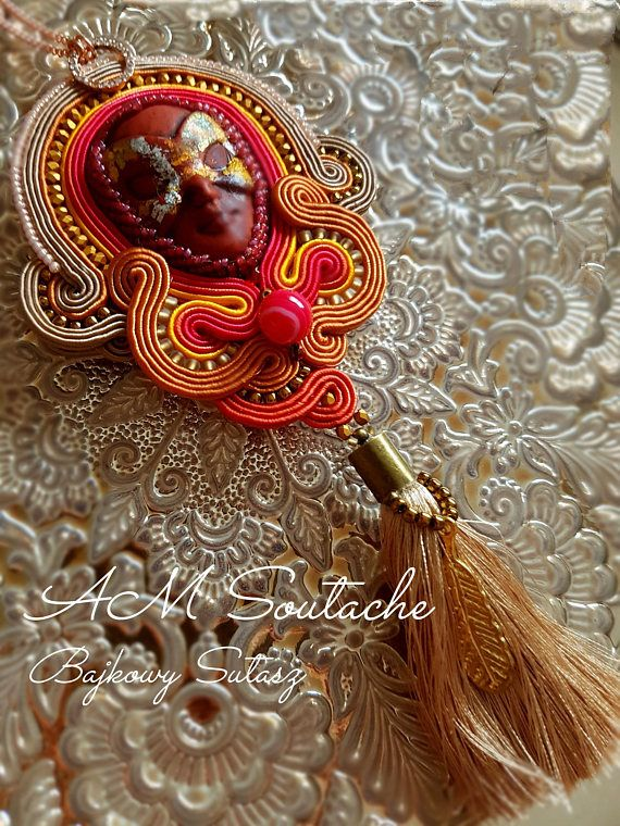 Soutache pendant in bright autumn colours on Long gold chain. Ceramic mask surrounded by toho beads. Gold tassels with pink agate sound stones