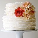 A four-layer cake is draped with white fondant and topped with hand-made sugar orchids and roses.White Cake