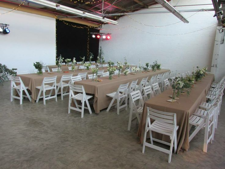 Spring wedding set up - trestle tables, white folding chairs, white flowers in jars