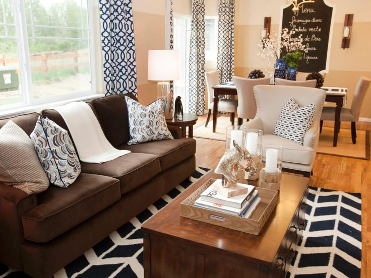 Bold, graphic, black-and-white patterned curtains, pillows and a rug fill this white living room, creating a unique space. A chalkboard menu hangs over the dining table for a charming touch.