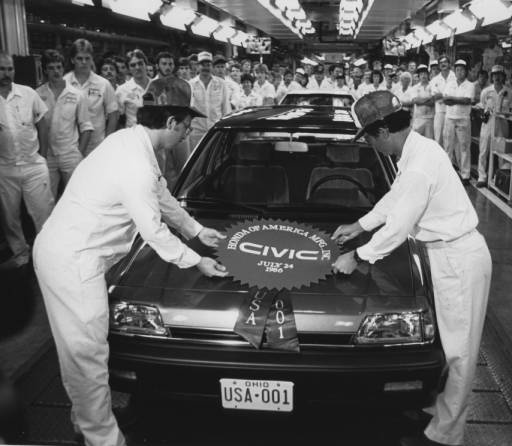 The first Honda Civic to be manufactured in the United States comes off the assembly line July 24, 186 at the Honda of America Manufacturing Auto Plant in Marysville OH. Affixing the seal are Keith Beachy, Plain City and Hideo Yokoyama, Worthington, Civic project leaders.