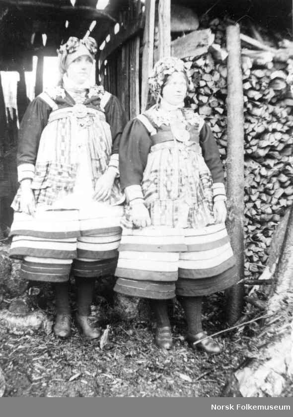 Digitalt Museum - To kvinner foran en vedstabel. De er kledd i brudedrakt fra Setesdal i Aust-Agder.