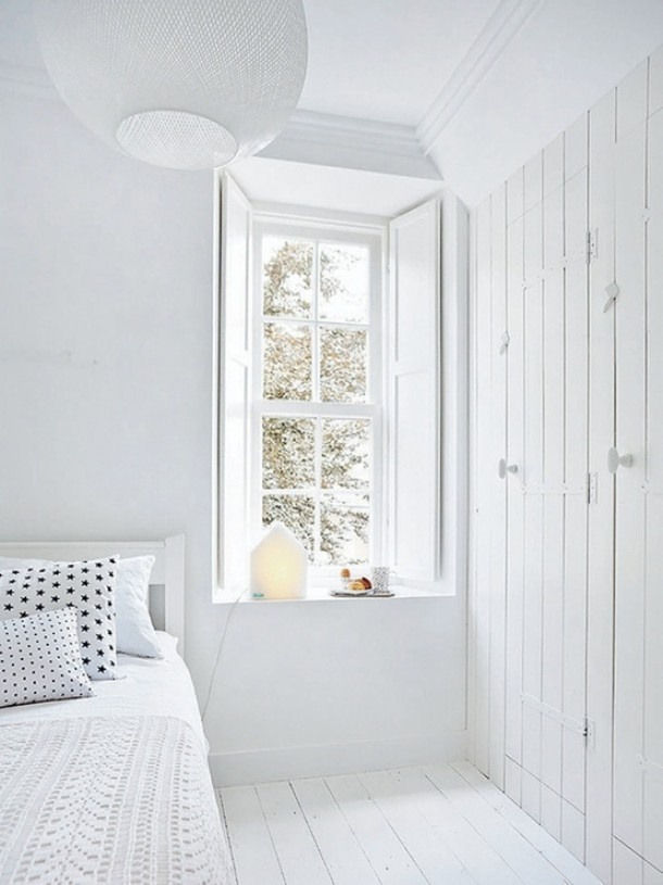 Witte slaapkamer: raam met diepe vensterbank en mooie houten luiken en inbouwkasten. Door Tiara