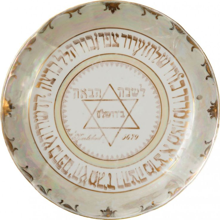 """Passover Seder plate. Carlsbad, Czechoslovakia, 1919. Porcelain (pearl glazing); text and decoration in gold. Rim decorated with vegetal and geometric patterns, in gold. The fifteen """"Simanim"""" of the Seder are inscribed in golden ink, and in the center of the plate appear the inscription """"Next Year in Jerusalem"""" (Hebrew; the word """"Jerusalem"""" is in the center of a Star of David), the location and year. Diameter: 33.5 cm. Good condition. Inscription and golden decorations are worn."""