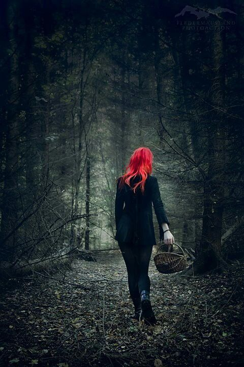 The Red Hair In Contrast With All Of The Dark Colors In