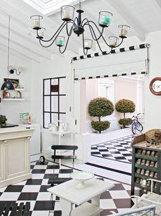 Lámparas galponeras, araña de techo y pequeña mesa de madera con sillas haciendo juego: todo es blanco y negro en este quincho. El toque lúdico lo da un viejo juego de sapo.