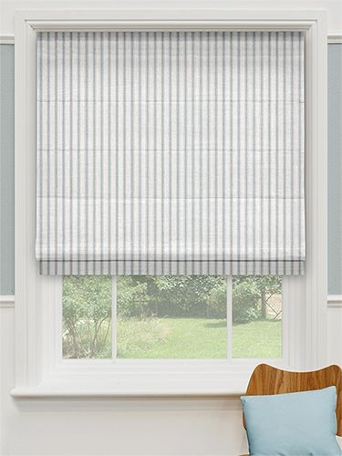 This light and airy, linen-like roman blind has a simple vertical striped pattern in a faded blend of white and pastel blue that gives it a traditional, coastal feel.