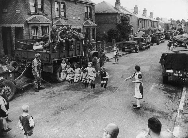 İp atlayan çocuklara yardım eden Amerikan askerleri, İngiltere, 1944.