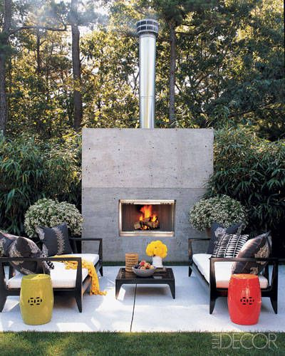The shaded terrace of designer Eric Hughes's Hamptons ranch house features a sleek poured-concrete fireplace. With furniture by DelGreco & Company and ceramic garden stools by Mecox Gardens, the outdoor room is ideal for sipping cocktails on cool summer nights.