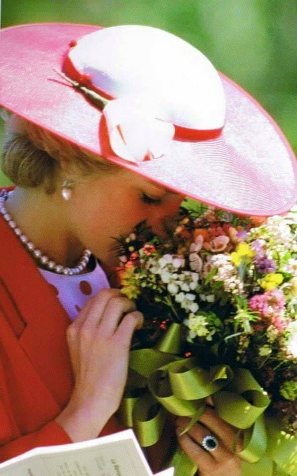 Princess Diana...beautiful picture. She couldn't resist the fragrant and beautiful bouquet.The colors of her attire as well as the hat enhance the vibrant colors of the flowers.