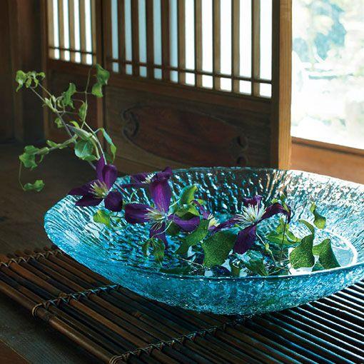 津軽びいどろ  水盤 ガラスの柔らかな質感は、昔からの製法である宙吹きのテクニックで透明感のあるガラスプレートに。水面を眺めながら花を見せる生け方は見た目に涼しげです。ゆとりとくつろぎをもたらす水盤を暮らしに取り入れてみては。