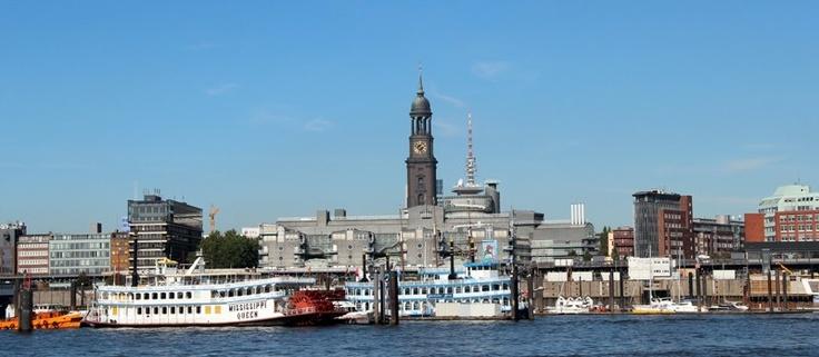 Panorama Aufnahme vom Hamburger Hafen mit Blick auf die Landungsbrücken. Im Hintergrund sieht man die Mississippi Queen, den Hamburger Michel sowie den Fernsehturm.