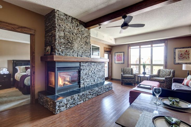 Spacious living and dining area with Knotty Alder wood accents, maple hardwood floors and a double sided gas fireplace