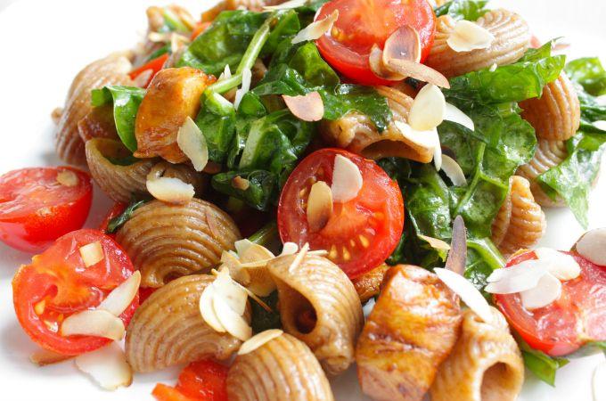 Deze heerlijke zomerse pasta met honingkip, spinazie, paprika en cherry tomaten staat in een handomdraai op tafel. Kijk hier voor het recept.