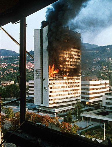 "And that happened right before our very eyes in Europe...  ""Bosnian parliament building burns after being hit by Serbian tank fire during the Siege of Sarajevo."""